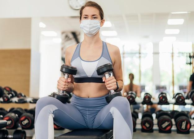 Mulher com máscara fazendo exercícios na academia durante a pandemia