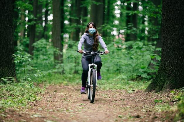 Mulher com máscara médica anda de bicicleta no parque