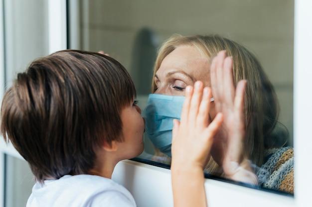 Mulher com máscara médica beijando um sobrinho pela janela em quarentena