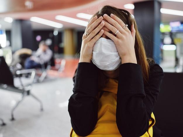 Mulher com máscara médica cobre o rosto com as mãos fadiga voo atraso aeroporto