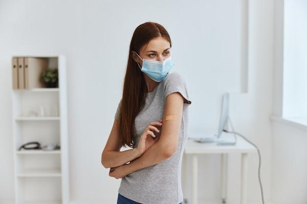Mulher com máscara médica de hospital com gesso germicida no ombro, olhando pela janela cobiçosa