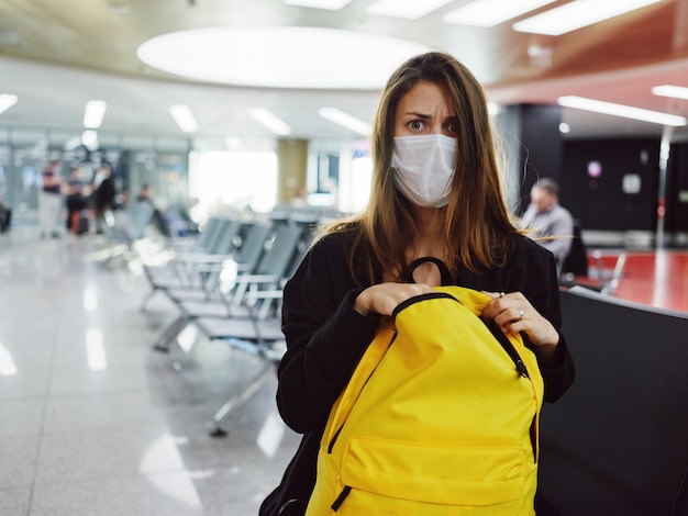 Mulher com máscara médica do aeroporto de batalha de bagagem olhar descontente