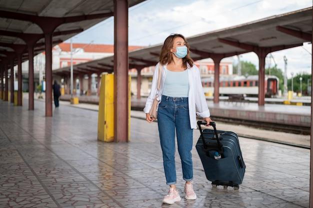Mulher com máscara médica e bagagem na estação de trem pública