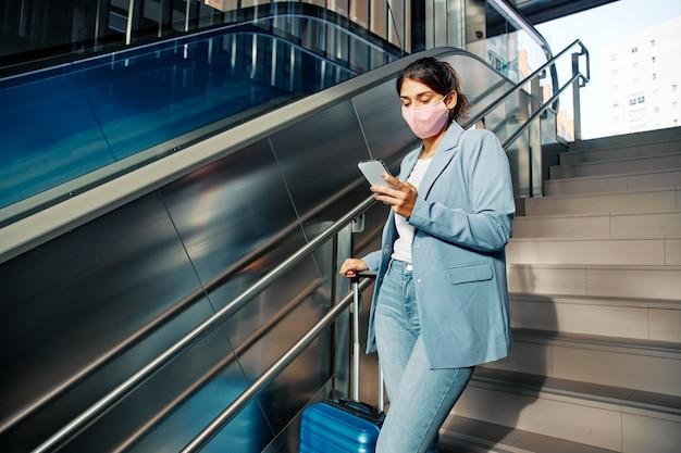 Mulher com máscara médica e bagagem usando smartphone enquanto descia escadas durante a pandemia