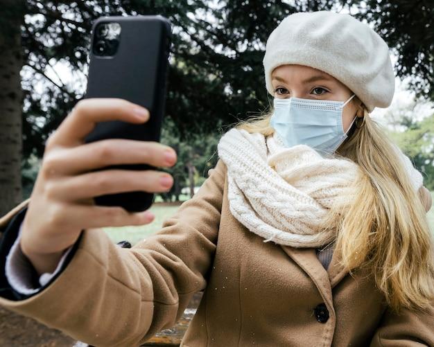 Mulher com máscara médica e boina tirando selfie no parque durante o inverno