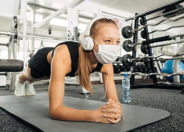 Mulher com máscara médica e fones de ouvido malhando na academia