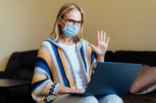 Mulher com máscara médica e laptop em quarentena