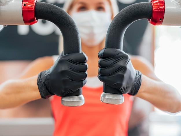 Mulher com máscara médica e luvas no treino de ginástica