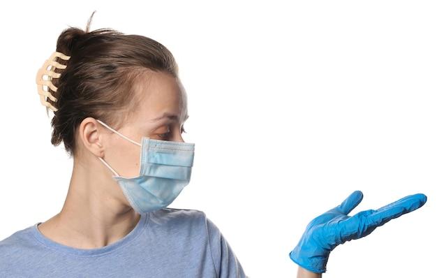Mulher com máscara médica e luvas segura a palma da mão para o espaço da cópia isolado no branco