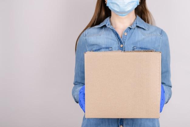 Mulher com máscara médica e luvas segurando uma caixa de papelão isolada