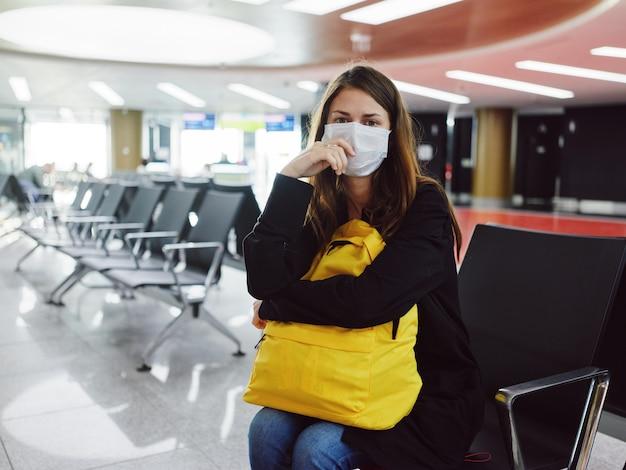 Mulher com máscara médica e mochila amarela descontente com o atraso do voo
