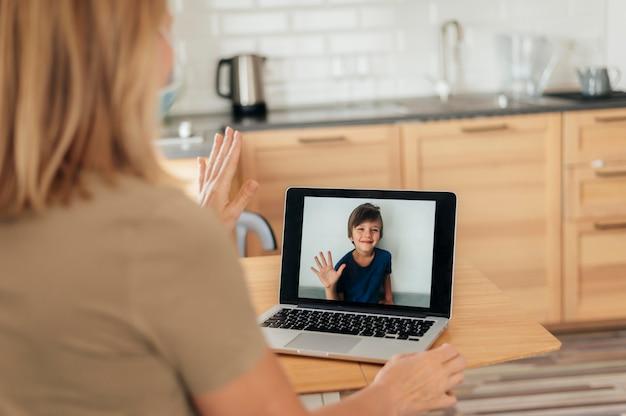 Mulher com máscara médica e sobrinho de videochamada de laptop durante quarentena