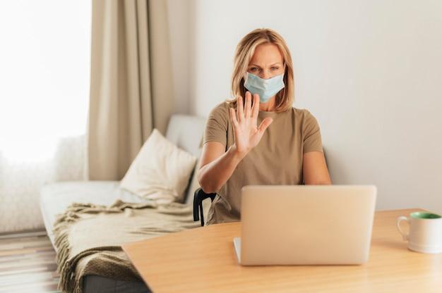 Mulher com máscara médica e videochamada em laptop durante quarentena