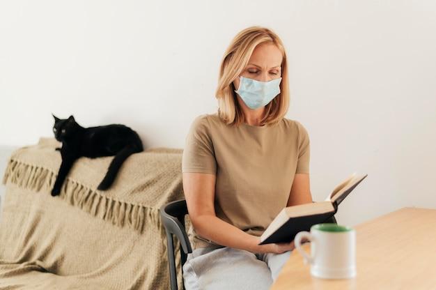 Mulher com máscara médica em casa com gato lendo durante a quarentena