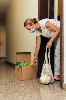 Mulher com máscara médica em casa fazendo compras na quarentena