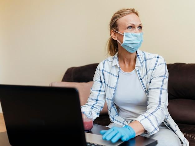 Mulher com máscara médica em casa trabalhando no laptop durante a quarentena