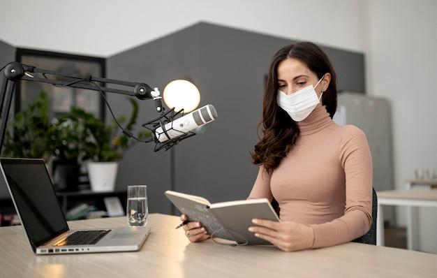 Mulher com máscara médica em um estúdio de rádio com microfone e laptop