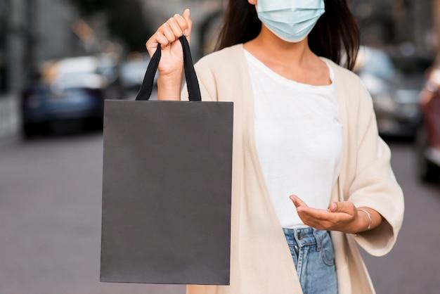 Mulher com máscara médica exibindo sacola de compras que está segurando