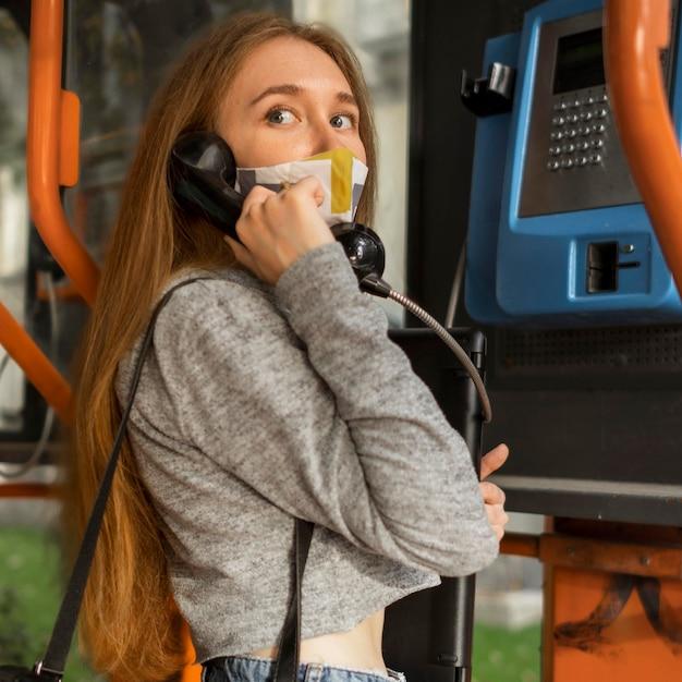 Mulher com máscara médica falando em um telefone público