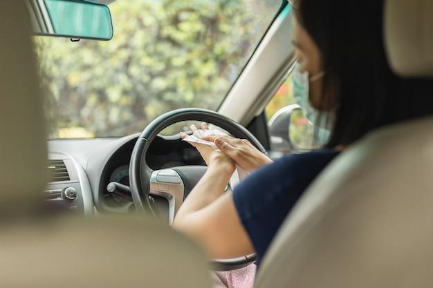 Mulher com máscara médica limpando as mãos com lenços umedecidos enquanto está sentada no carro