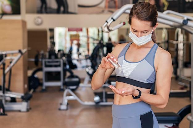 Mulher com máscara médica na academia usando desinfetante para as mãos