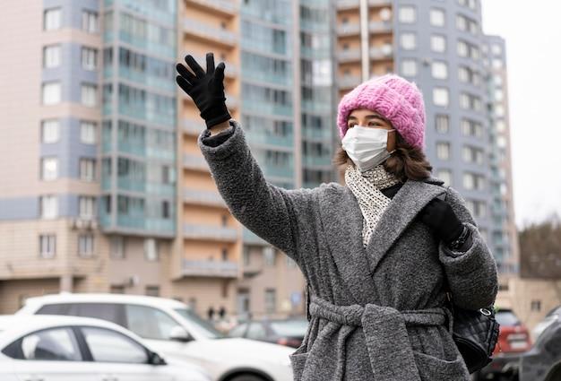 Mulher com máscara médica na cidade acenando