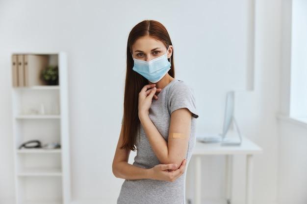 Mulher com máscara médica no hospital com gesso germicida no ombro saúde imunidade passaporte covid