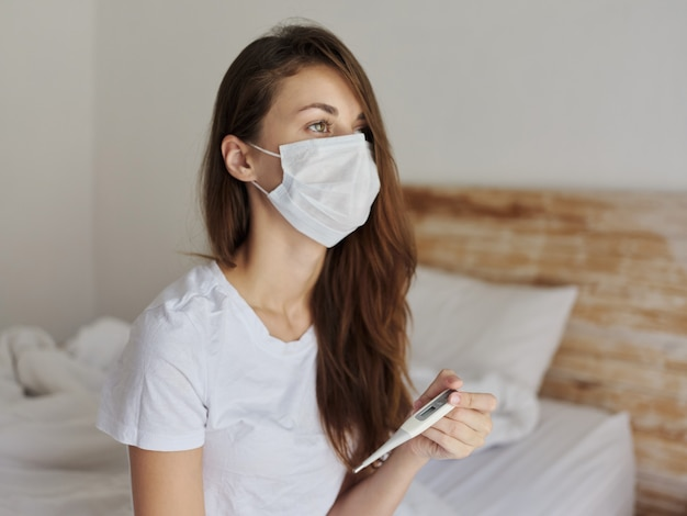 Mulher com máscara médica no quarto verifica a temperatura com um termômetro