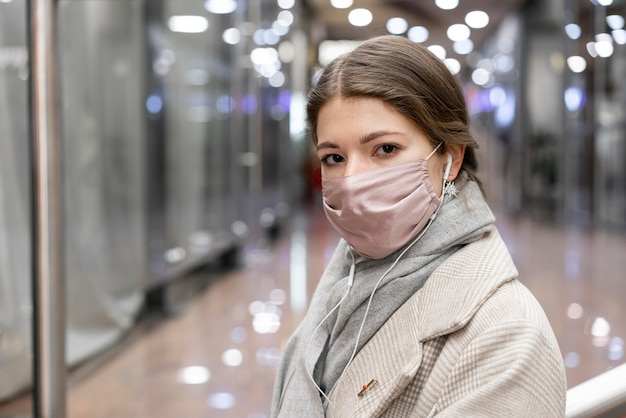 Mulher com máscara médica no shopping da cidade
