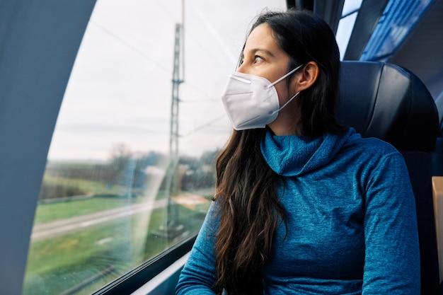Mulher com máscara médica olhando pela janela do trem