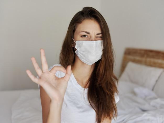 Mulher com máscara médica piscando gesto positivo com a mão