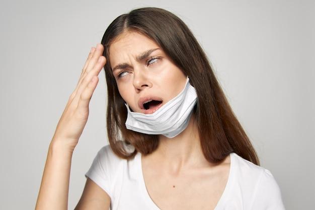 Mulher com máscara médica revira os olhos com a mão perto da cabeça
