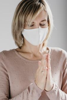 Mulher com máscara médica rezando