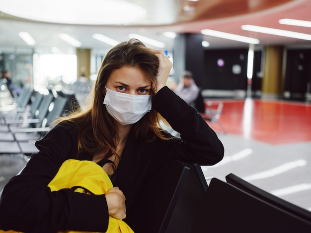 Mulher com máscara médica segura a mão na cabeça do passageiro do aeroporto com mochila amarela