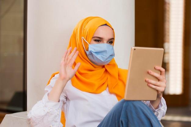 Mulher com máscara médica segurando o tablet