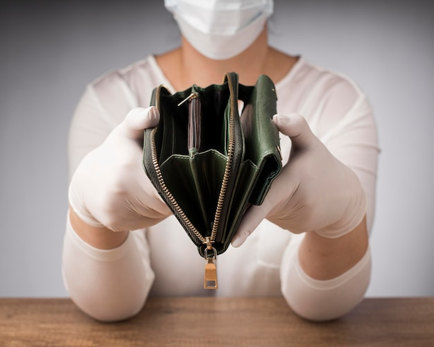 Mulher com máscara médica segurando uma carteira vazia