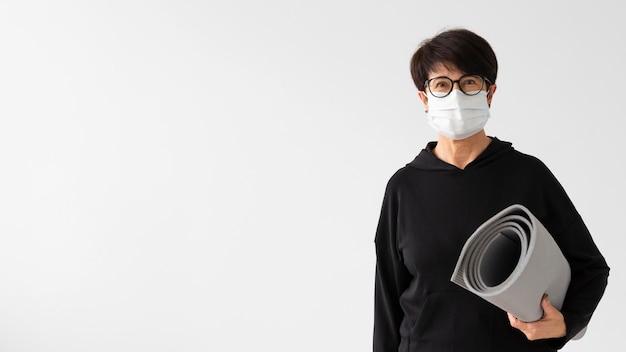 Mulher com máscara médica segurando uma esteira de ginástica