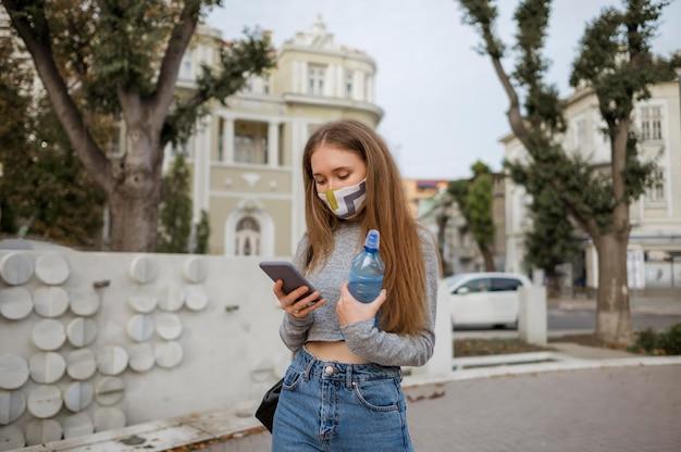 Mulher com máscara médica segurando uma garrafa de água