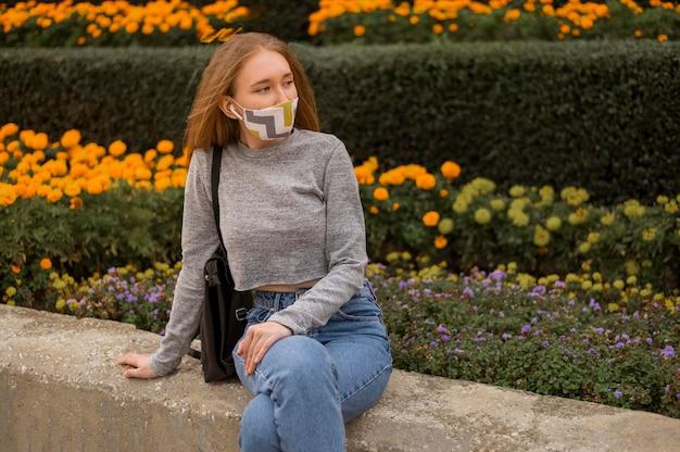 Mulher com máscara médica sentada ao lado de um jardim com máscara médica