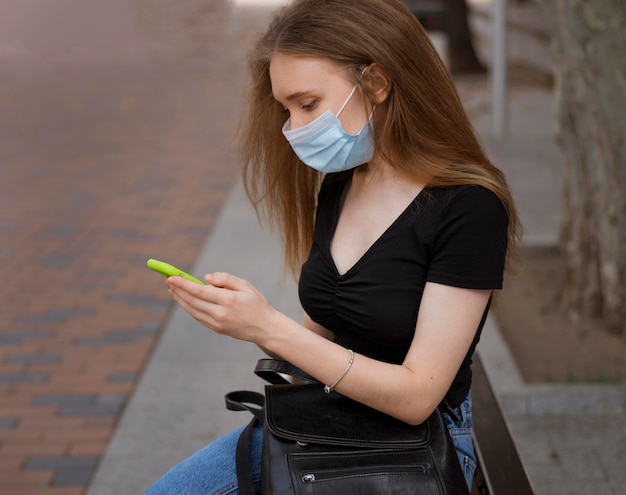 Mulher com máscara médica sentada em um banco ao ar livre