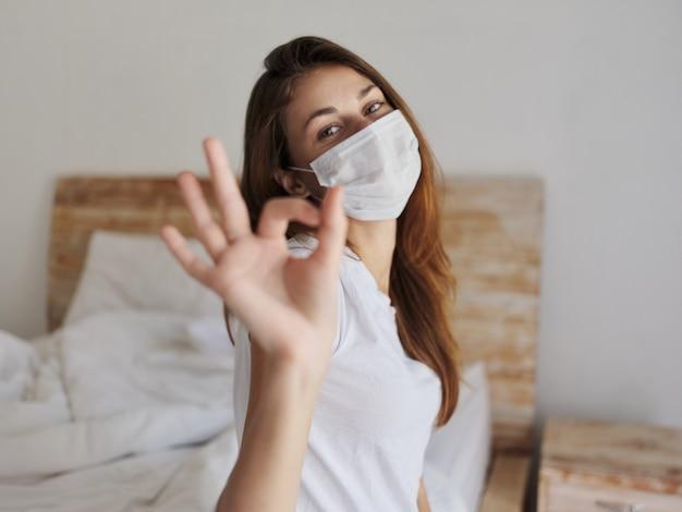 Mulher com máscara médica, sentada na cama, mostrando gestos positivos com as mãos