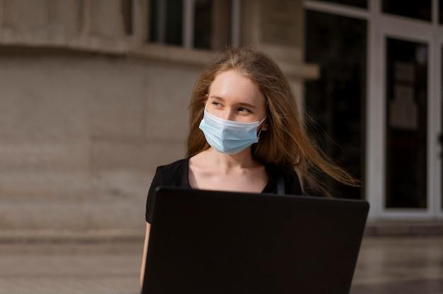 Mulher com máscara médica sentada na escada do lado de fora enquanto trabalha no laptop
