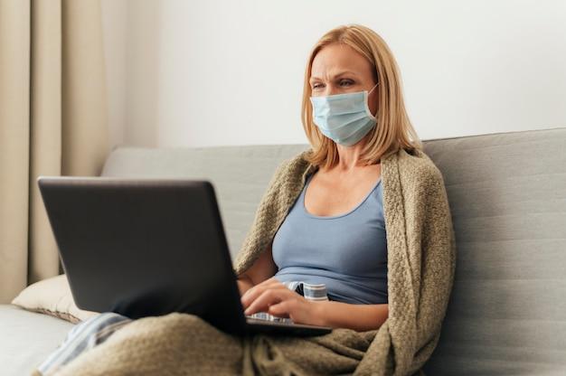 Mulher com máscara médica trabalhando em um laptop em casa durante o auto-isolamento