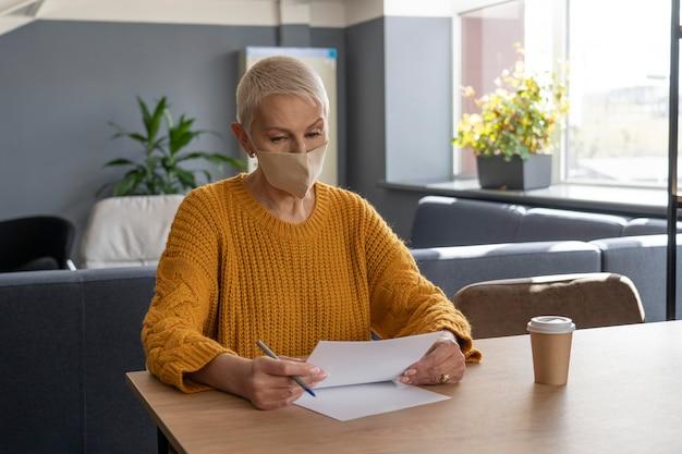 Mulher com máscara médica trabalhando