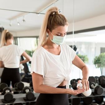 Mulher com máscara médica usando desinfetante para as mãos na academia