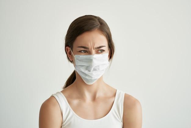 Mulher com máscara médica usando o vírus da pandemia de camiseta branca. foto de alta qualidade