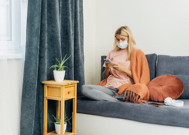 Mulher com máscara médica usando smartphone em casa durante a pandemia