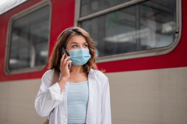 Mulher com máscara médica usando smartphone na estação de trem pública