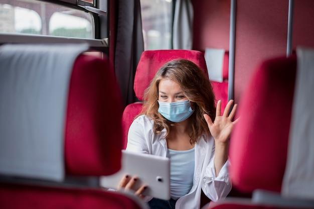 Mulher com máscara médica usando tablet para videochamada enquanto viaja no trem público