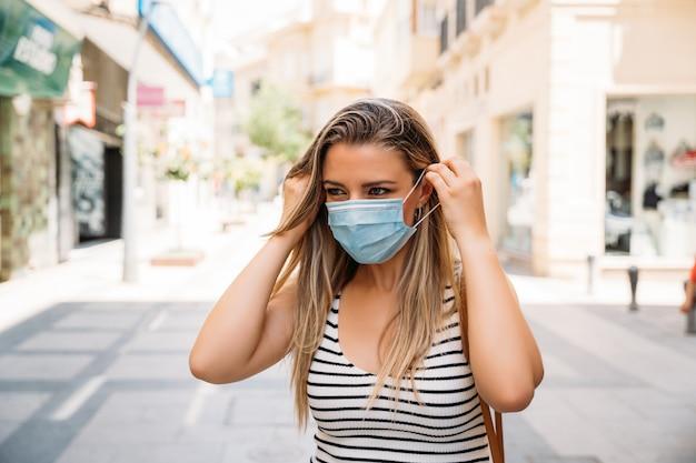 Mulher com máscara na cidade, usando seu telefone celular durante a pandemia de coronavírus